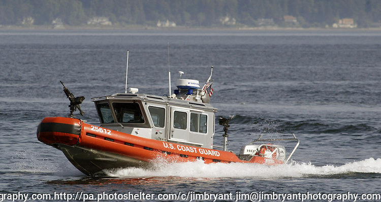 A United State Coast Guard Patrol boat performs escort service for a Washington State ferry near Seattle on August 20, 2009.  The personnel and boats, from the 13th Coast Guard District, provide protection from possible terrorists attacks in support of the Homeland Security for ferries operating from Seattle area ferry terminals to those on the Kitsap Peninsula, Vashion Island, and Bainbridge Island.    © 2009. All Rights Reserved. Jim Bryant