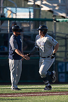 Tri-City Dust Devils first baseman Justin Paulsen (24) high fives manager Mike McCoy (14) as he rounds the bases after hitting a home run during a Northwest League game against the Everett AquaSox at Everett Memorial Stadium on September 3, 2018 in Everett, Washington. The Everett AquaSox defeated the Tri-City Dust Devils by a score of 8-3. (Zachary Lucy/Four Seam Images)