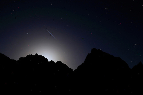 The bright light from a full moon appears along the rim of Zion Canyon at Zion National Park, Utah along with the streaking light of a jet aircraft