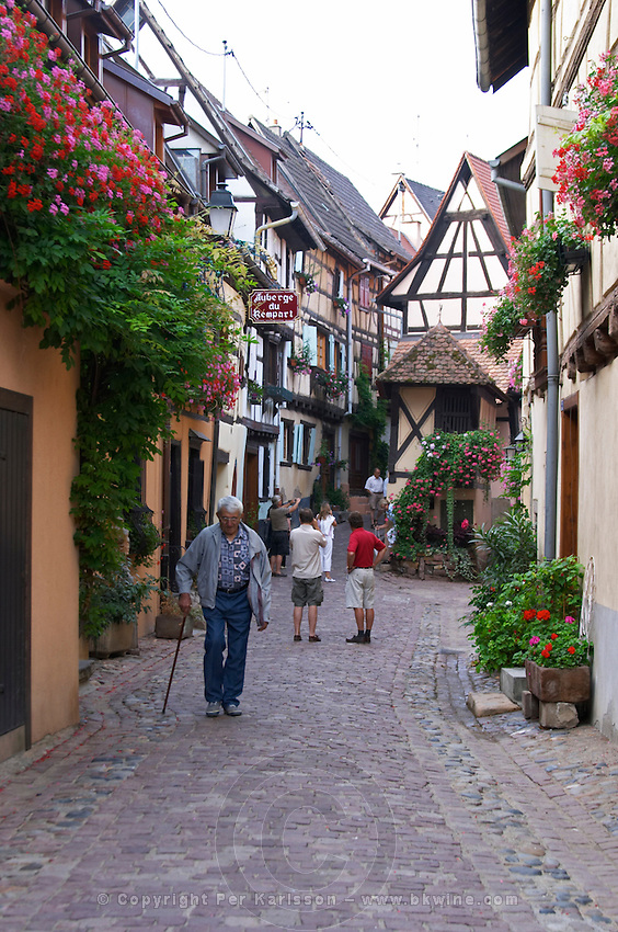 a narrow street with people eguisheim alsace france