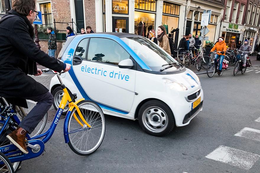 Nederland, Amsterdam, 20150313<br /> verkeer, kruispunt, fietser, fietsers, binnenstad, centrum, electrische auto, ov fiets, <br /> Foto: (c) Michiel Wijnbergh