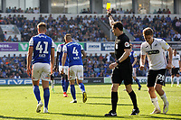 James Bree of Ipswich Town (L) sees a yellow card by referee Darren England during the Sky Bet Championship match between Ipswich Town an Swansea City at Portman Road Stadium, Ipswich, England, UK. Monday 22 April 2019