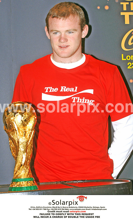 ALL ROUND PICTURES FROM SOLARPIX.COM..Wayne Rooney comes within inches of the football World Cup during an interview at Old Billingsgate in central London on 23.03.06.  The famous trophy was on a pre-tournament promotional tour before heading for Germany this summer.  Despite FIFA officials bending the 'no touch rule' for the young England star, Rooney declined to hold the cup in case it jinxed his teams chances of winning the tournament. Job Ref: 2210/FN1. MUST CREDIT SOLARPIX.COM OR DOUBLE FEE WILL BE CHARGED.