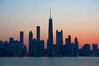 "Dusk view of Chicago's magnificent skyline as seen from Lake Michigan. The architecture of Chicago has influenced and reflected the history of American architecture. The city of Chicago, Illinois features prominent buildings in a variety of styles by many important architects. Since most buildings within the downtown area were destroyed by the Great Chicago Fire in 1871, Chicago buildings are noted for their originality rather than their antiquity..Beginning in the early 1880s, architectural pioneers of the Chicago School explored steel-frame construction and, in the 1890s, the use of large areas of plate glass. These were among the first modern skyscrapers and amongst their most famous architects were William LeBaron, John Wellborn Root Sr., Daniel Burnham and Charles Atwood. Louis Sullivan was perhaps the city's most philosophical architect. Realizing that the skyscraper represented a new form of architecture, he discarded historical precedent and designed buildings that emphasized their vertical nature. This new form of architecture, by Jenney, Burnham, Sullivan, and others, became known as the ""Commercial Style,"" but it was called the ""Chicago School"" by later historians..Since 1963, a ""Second Chicago School"" emerged, largely due to the ideas of structural engineer Fazlur Khan. Some of Chicago's skyscrapers such as the John Hancock Center, Willis Tower (formerly known as the Sears Tower) and The Trump International Hotel and Tower are amongst the tallest buildings in the world."