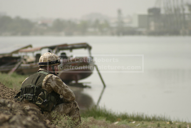 With Basrah City in the background and after several hours of patrolling in the Iraqi sun, a British soldier takes a moment to relax on the banks of the Shatt al-Arab river.