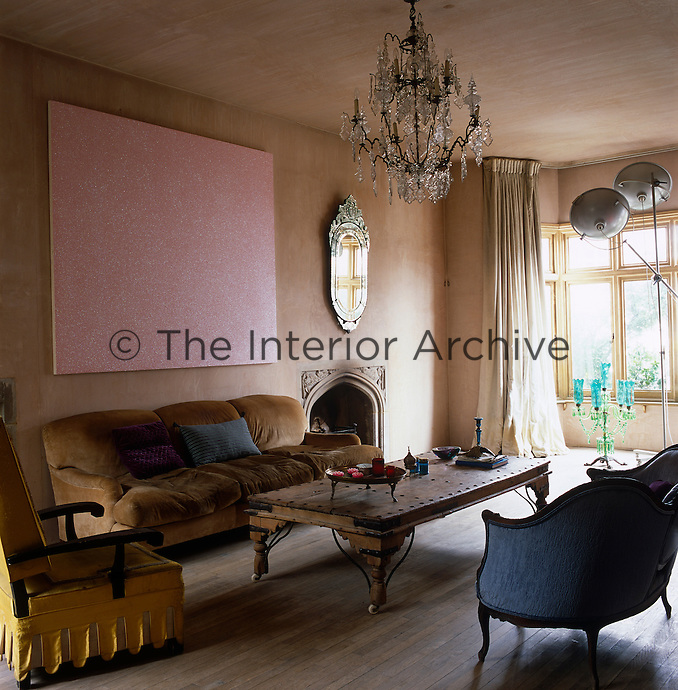 Pink plaster walls and limed oak floors provide a unifying backdrop to an eclectic mix of objects in this living room