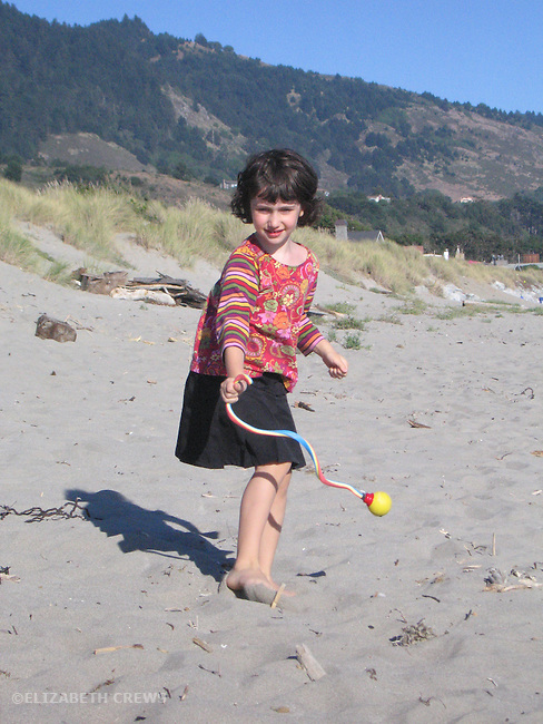 Stinson Beach CA Girl, five-years-old experimenting with ball rocket while playing at beach MR