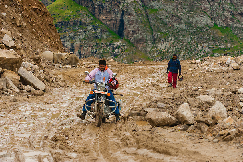 Motoryclist rides in the mud on Rohtang Pass in Himachal Pradesh, India. The 13,000 foot pass, near Manali, in the Pir Panjal Range of the Himalayas connects the Kullu Valley with the Lahaul and Spiti Valleys.