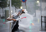 A woman clings on to a street sign as typhoon Roke blows through Tokyo, Japan on 21 Sept. 2011. The typhoon was reported to have killed at least 4 people and by evening was heading toward Fukushima's stricken nuclear plant, where it is feared heavy rains may force radioactive water into the sea. .Photographer: ROBERT GILHOOLY