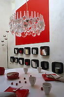 A quirky chandelier made from magnifying glasses hangs over the Saarinen tulip dining table in this red and white living space