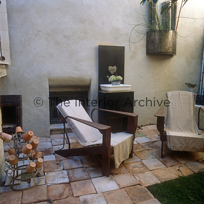 Two wooden armchairs are placed on the paved patio of a small town courtyard garden.