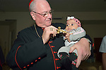 Cardinal Timothy Dolan, the archbishop of New York, holds a baby during a visit to a camp for internally displaced families in Ankawa, near Erbil, Iraq, on April 9, 2016. Dolan, chair of the Catholic Near East Welfare Association, is in Iraqi Kurdistan with other church leaders to visit with Christians and others displaced by ISIS.