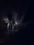 Young woman in underwear walking with a candle holder on a staircase in a house at night
