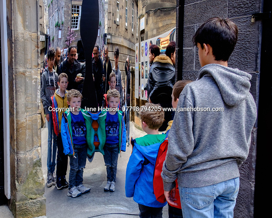 Edinburgh, UK. 15.04.2017. Boys having fun with distorting mirrors, outside the Camera Obscura, on the Royal Mile. Photograph © Jane Hobson.