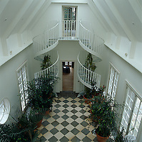 A double spiral staircase leading to the upper floor in this double-height hallway
