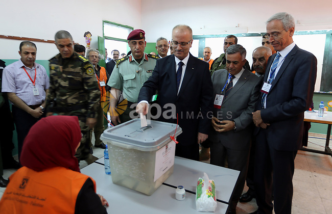 Palestinian Prime Minister Rami Hamdallah casts his ballot at a polling station during municipal elections in the northern West Bank town of Anabta, near Tulkarm May 13, 2017. Photo by Prime Minister Office