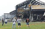 Foto: VidiPhoto<br /> <br /> ERICHEM &ndash; De brandweer is vrijdag nog lange tijd bezig geweest met het nablussen van de enorme brand in de stallen van De Knorhof aan de Erichemsewal in Erichem, bij Tiel. De brand is volgens de brandweer ontstaan in een stal achter het woonhuis. De oorzaak is nog niet bekend. Door niet ge&iuml;mpregneerde isolatiepanelen en de zogenoemde luchtwassers, die stank in de omgeving tegengaan, verspreidde de brand zich razendsnel door alle stallen. Binnen een half uur was het vuur verspreid door het hele complex. Daarbij kwamen 16.000 varkens om. Het bedrijf heeft vergunning voor 20.000 varkens. Het enorme complex telt ongeveer 120 bij 120 meter. Bij de brand is asbest in de directe omgeving vrijgekomen. Een extern bedrijf brengt het verspreidingsgebied in kaart. Verderop in het dorp zijn roetdeeltjes neergedaald. De brand in Erichem is de grootste varkensbrand ooit in ons land. Foto: Het personeel aanschouwt de ravage.