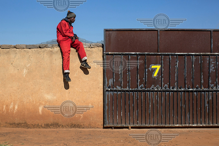 A member of the Red Ants sits on the wall of a house from where the occupants are being evicted.<br />