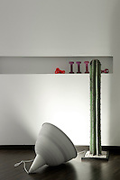 A green metal sculptured cactus is lit by a spotlight in a corner of one of the bedrooms