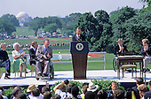 United States President George H. W. Bush makes remarks prior to signing the Americans with Disabilities Act of 1990 into law during a ceremony on the South Lawn of the White House in Washington, D.C. on July 26, 1990. Pictured, on stage, (left to right): Reverend Harold Wilke, first lady Barbara Bush, U.S. Vice President Dan Quayle, Evan Kemp, President Bush, Justin Dart, and Sandra Parrino.  The act prohibited employer discrimination on the basis of disability. <br /> Credit: Ron Sachs / CNP
