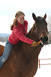 A young woman feeds a carrot to her horse in Wilson, Wyoming.