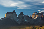 Sunset light illuminates the yellow granite face of Monte Almirante Nieto.  A cloud casts a shadow, creating a dark band across the face.  At left are the Curenos del Paine, with Monte Almirante Nieto on the right.  Between the Cuernos and Monte Almirante Nieto, one can see the tips of Torre Sur and Torre Central.  Torres del Paine National Park in Patagonia, Chile.  A UNESCO World Biosphere Reserve.