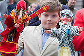 Covent Garden, London, UK. 11 May 2014. A young puppeteer holds up Punch and Judy puppets. The festival starts with a procession around the streets of Covent Garden. The Covent Garden May Fayre and Puppet Festival takes place at St Paul's Church.