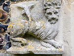 Weathered lion carving in limestone rock on church wall