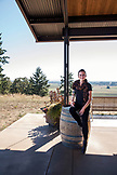 USA, Oregon, Willamette Valley, portrait of a beautiful young woman with a glass of red wine at the tasting room at Sotor Vineyards and Winery, Carlton
