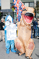 "A person wearing a Left Shark costume holds a sign reading ""Straight Lives Matter"" and a man wears an inflatable Tyrannosaurus Rex costume while holding a Trump 2020 flag as they take part in the Straight Pride Parade in Boston, Massachusetts, on Sat., August 31, 2019."