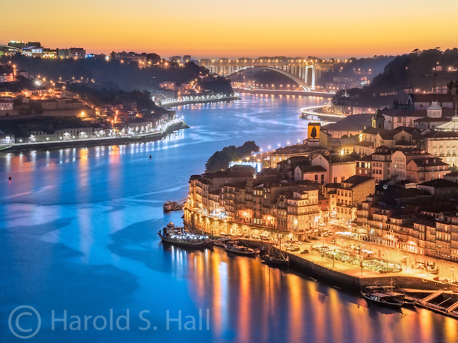 Evening in the Ribeira section of Porto, Portugal.  Standing out is a yellow billboard of a silhouetted  figure called the Sandman.  This is brand of local wine.  On a building next to the Douro River you might see the name CÁLEM which is another wine of the area.