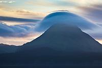 Clouds roll over a mountain along the shores of Kodiak Island, Alaska.