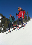 Young couple snowshoeing down a steep hill in Rocky Mtns, CO