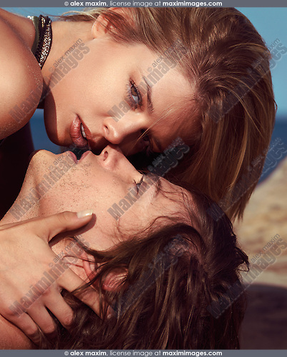 Sensual portrait of a young couple kissing on the beach lying in the sand, closeup of faces