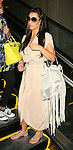 April 2nd  2012  ...Kim Kardashian & family arriving at the LAX  Los Angeles airport. Kim was carrying a big white see through fringe lace purse handbag with long strings hanging from it. Kris Jenner was carrying a yellow purse ..AbilityFilms@yahoo.com.805-427-3519.www.AbilityFilms.com..