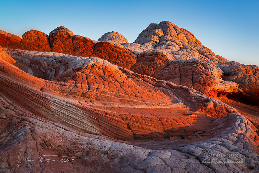 Flowing Rock: Sunset at White Pocket ©2017 James D Peterson.  Illuminated by the last rays of a warm sunset, these unique rock formations in Arizona's Vermilion Cliffs National Monument look like they're cascading headlong down a flooding river.