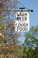"""""""Warm beer, lousy food"""" jokey sign for the Merry Harriers public house, Hambledon, Surrey."""