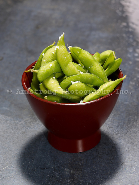 A small red bowl with fresh edamame (soybean pods)