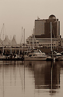 Canada Place and marina with boats and yachts reflected in the waters of Coal Harbor, Vancouver, BC.