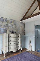 A bow-fronted Georgian chest of drawers in an attic bedroom with blue painted panelling and a distressed paint effect finish on the walls.