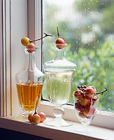 Crab apples are used as stoppers on a pair of decanters on this window sill