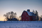 Montana, western, Flathead Valley, Kalispell. An old  red barn and cabin in a snowy landscape at dawn.