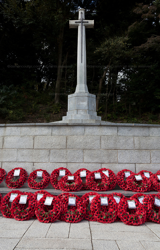 Wreaths of poppies laid around the Cross of Sacrifice during Remembrance Sunday ceremony at the Hodogaya, Commonwealth War Graves Cemetery in Hodogaya, Yokohama, Kanagawa, Japan. Sunday November 12th 2017. The Hodagaya Cemetery holds the remains of more than 1500 servicemen and women, from the Commonwealth but also from Holland and the United States, who died as prisoners of war or during the Allied occupation of Japan. Each year officials from the British and Commonwealth embassies, the British Legion and the British Chamber of Commerce honour the dead at a ceremony in this beautiful cemetery.