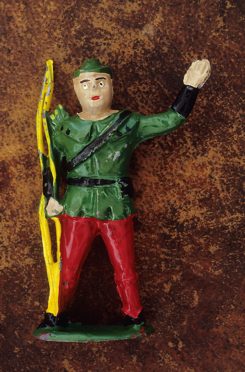 Toy lead model of Robin Hood in green top and hat with red trousers and yellow longbow waving and standing against scuffed leather