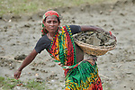 In order to raise her home a few inches, Shosida Begum carries dirt in a basket in West Fasura, a village on an island in the Brahmaputra River in northern Bangladesh. Severe flooding in August 2017 destroyed the island's crops but RDRS Bangladesh, a member of the ACT Alliance, provided emergency cash grants to vulnerable island families so they could reestablish their household economies and restart their lives.