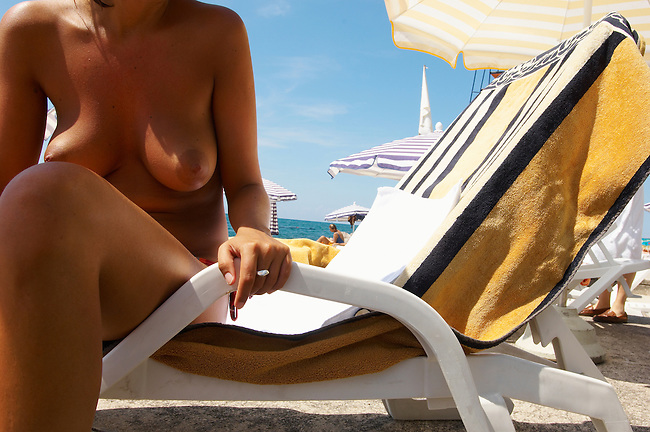 tanned topless sun bather sitting on a sun lounger