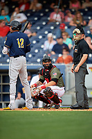 Nashville Sounds catcher Bruce Maxwell (36) looks into the dugout while Matt Juengel (12) and home plate umpire Junior Valentine await the next pitch during a game against the New Orleans Baby Cakes on April 30, 2017 at First Tennessee Park in Nashville, Tennessee.  The game was postponed due to inclement weather in the fourth inning.  (Mike Janes/Four Seam Images)