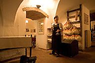 A waitress standing in front of famous Proscuitto hams in Parma Italy.