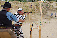 Participant dressed as a prisoner fires his weapon during the Cowboy Action Shooting European Championship in Dabas, Hungary on August 11, 2012. ATTILA VOLGYI