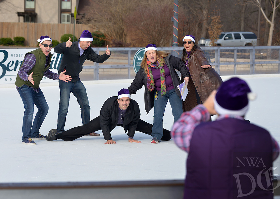 STAFF PHOTO BEN GOFF  @NWABenGoff -- 12/11/14 Seth Cobb, from left, Matt Schilb, Nolan Pedduto, Valerie Thomas and Anna Rodrigues strike a pose as Jennifer Allison takes a picture of them on the ice at The Rink at Lawrence Plaza as their team 'The Purple Pa rum pa pum pums,' compete with other teams of employees from Nielsen in a photo scavenger hunt team building exercise in Bentonville on Thursday Dec. 11, 2014.